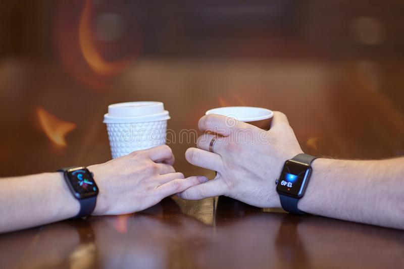 Two hands, male and female, both with equal electronic wrist watches, holding cups of coffee, white and black, on the wooden table royalty free stock photo