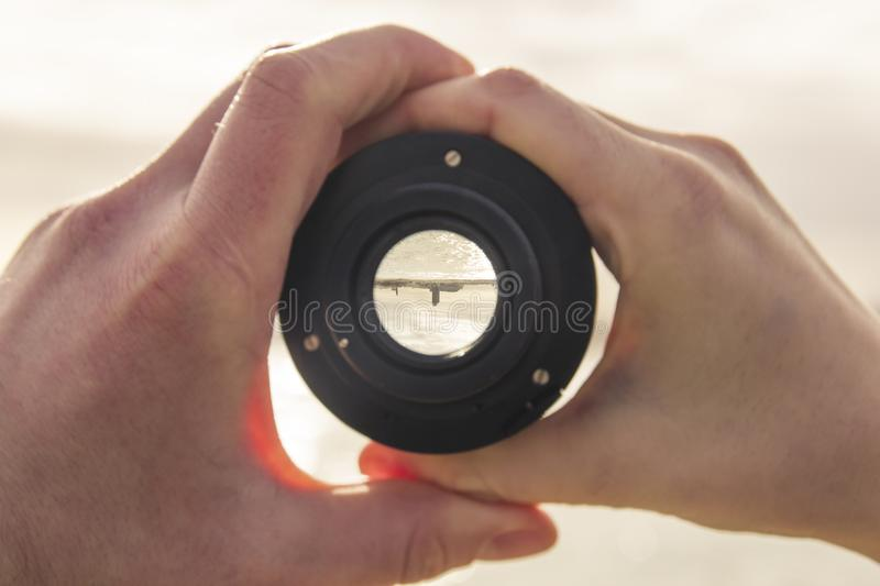 Two hands, male and female holding a camera lens, through the le royalty free stock photography