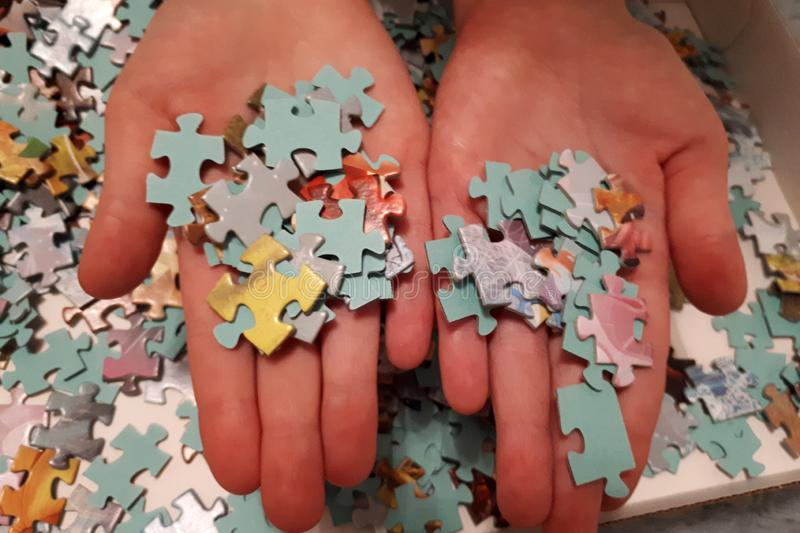 Two hands pick up puzzles stock photo