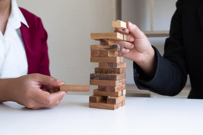 Two hands playing blocks wood game, gambling placing wooden block. Concept Risk of management and strategy plan stock photos