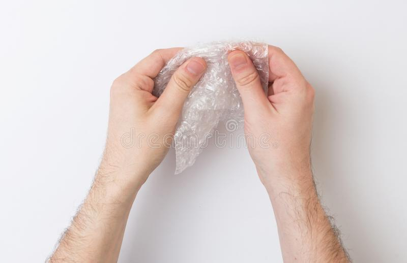Two hands popping bubblewrap on a white background. Two hands popping bubble wrap on a white background royalty free stock photo
