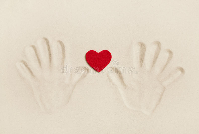Two hands print in the sand with a red heart. Symbol concept for royalty free stock image