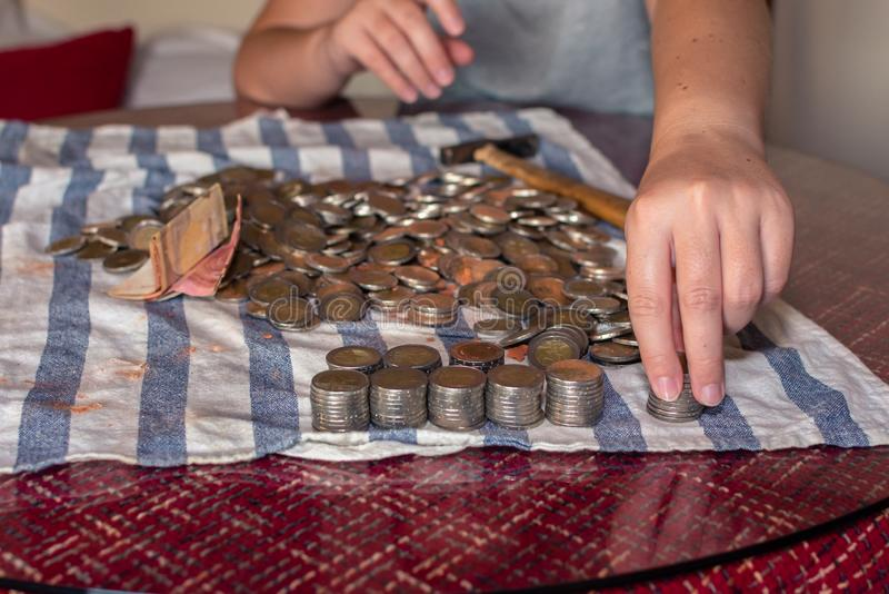 Two hands selecting coins from a piggy bank on a table stock photos