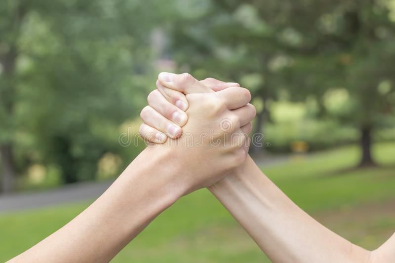 Two hands of teenagers are fighting among themselves in the park and the forest. In the sport of armwrestling. The concept of rivalry and violence between teens royalty free stock photos