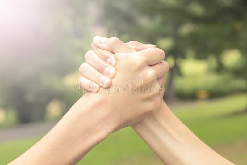Two hands of teenagers are fighting among themselves in the park and the forest. In the sport of armwrestling. The concept of rivalry and violence between teens stock photography