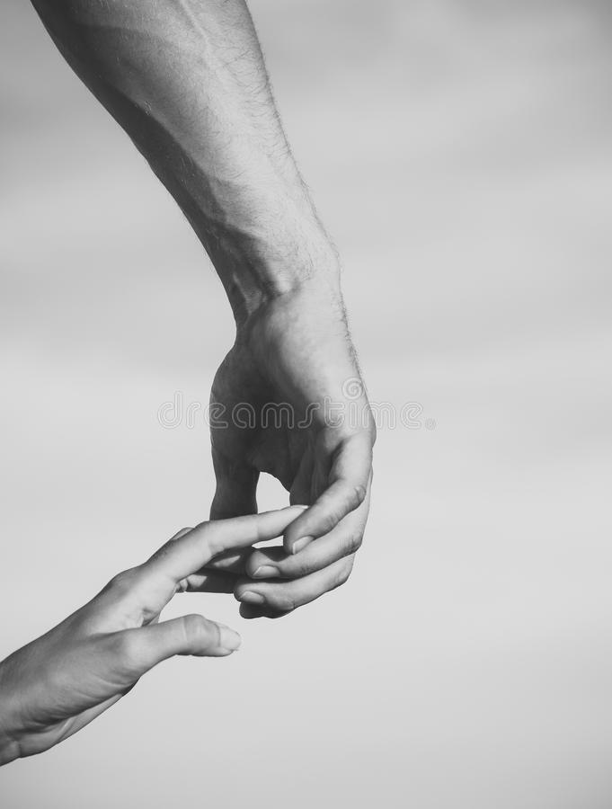 Two hands touching fingers on cloudy sky. Relationship and togetherness concept royalty free stock photo