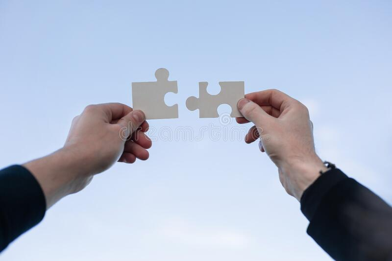 Two 2 hands trying to connect couple puzzle piece stock images
