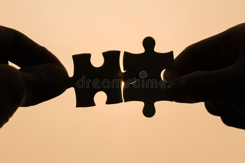Two Hands Trying To Connect Couple Puzzle Piece With Sunset
