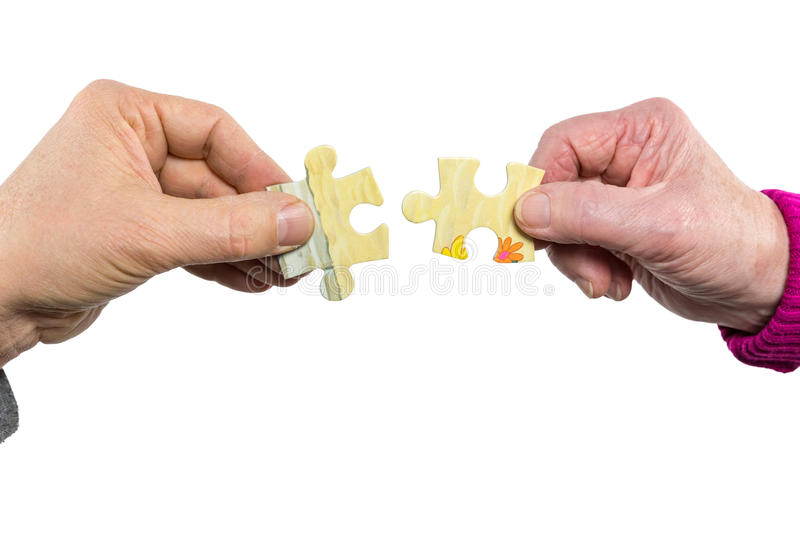 Two hands uniting fitting puzzle pieces royalty free stock photo