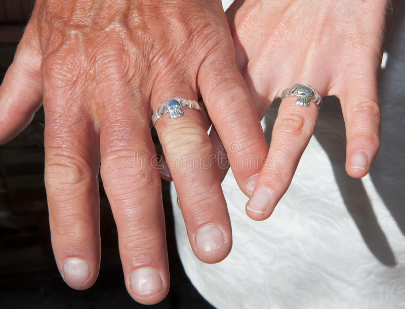 Two hands with wedding rings. Closeup shot of two hands wearing sliver wedding rings royalty free stock photos