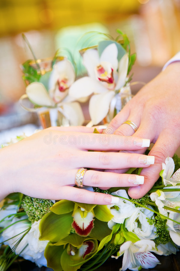 Two hands with wedding rings on the flower bouquet stock photo