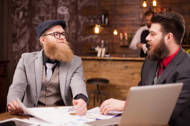 Two handsome bearded businessmen reaching to an agreement during their meeting in a coffee shop. royalty free stock photography