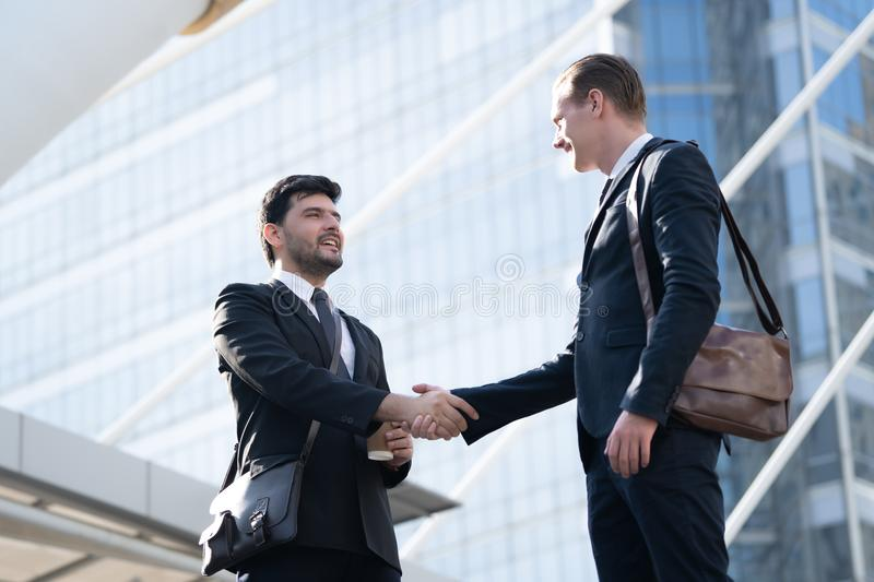 Two Handsome business man shaking hands outside modern office bu stock photos