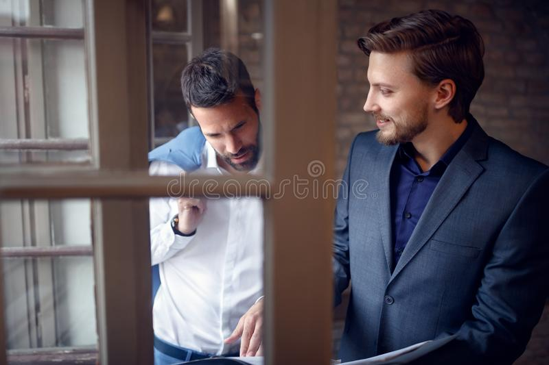 Two businessmen in office studding business offer stock photography