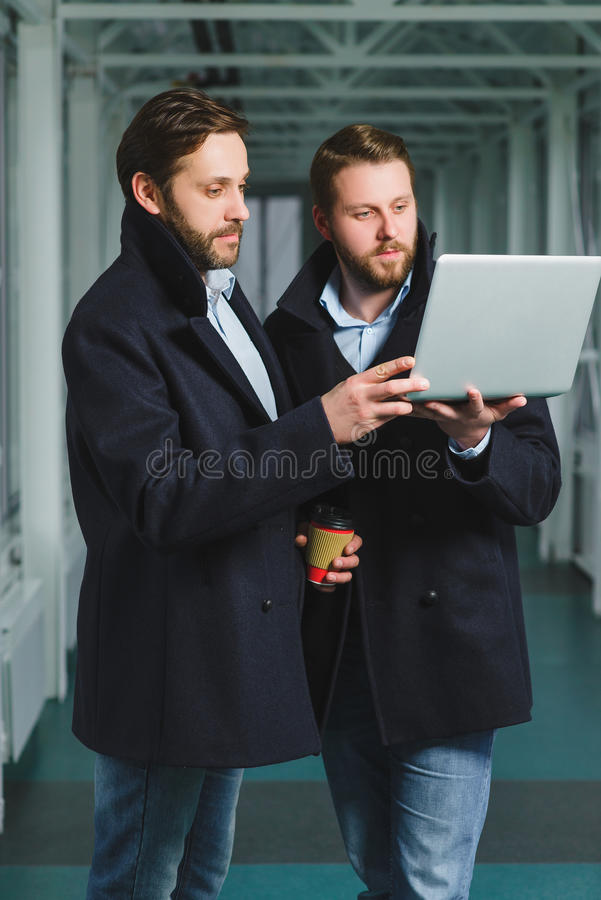 Two handsome businessmen working together on a project at lobby stock photo