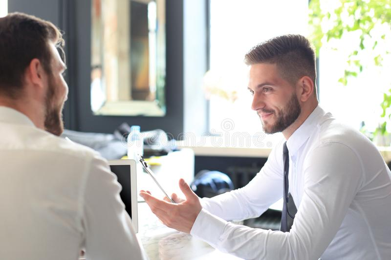 Two handsome businessmen working together on a project sitting at a table in the office royalty free stock photography