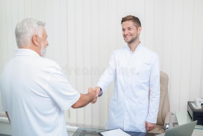Two handsome doctors shaking hands in light cabinet. royalty free stock images