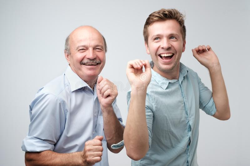 Two handsome male friends dancing on birthday party. stock photos