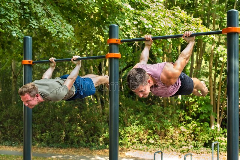 Two handsome man in back lever position doing calisthenics training street workout outdoors:. Young athletes hanging belly-down parallel to the ground, back royalty free stock photo
