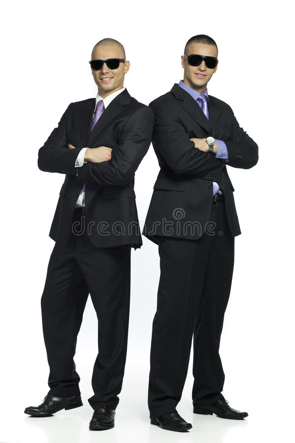 Two handsome men. Two handsome stylish men in suits wearing sunglasses stock photography