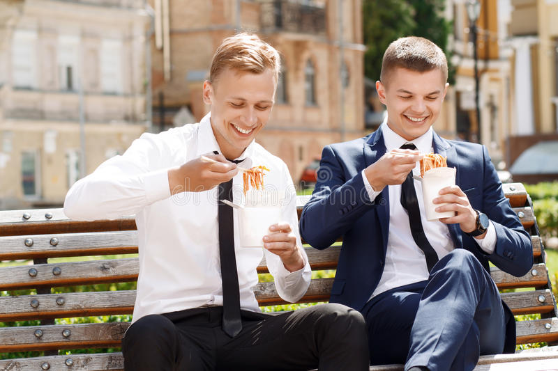 Two handsome men eating Chinese noodles. Pleasant moment. Pair of young handsome men in suits sitting on bench and eating Chinese noodles stock photos