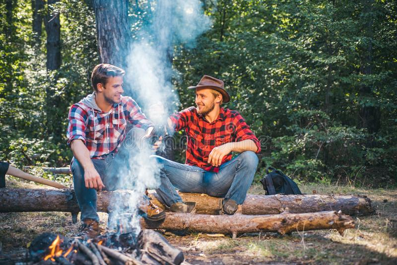 Two handsome men friends on camping near campfire. Friends men hikers watching fire together on camp. Two friends spend stock photo