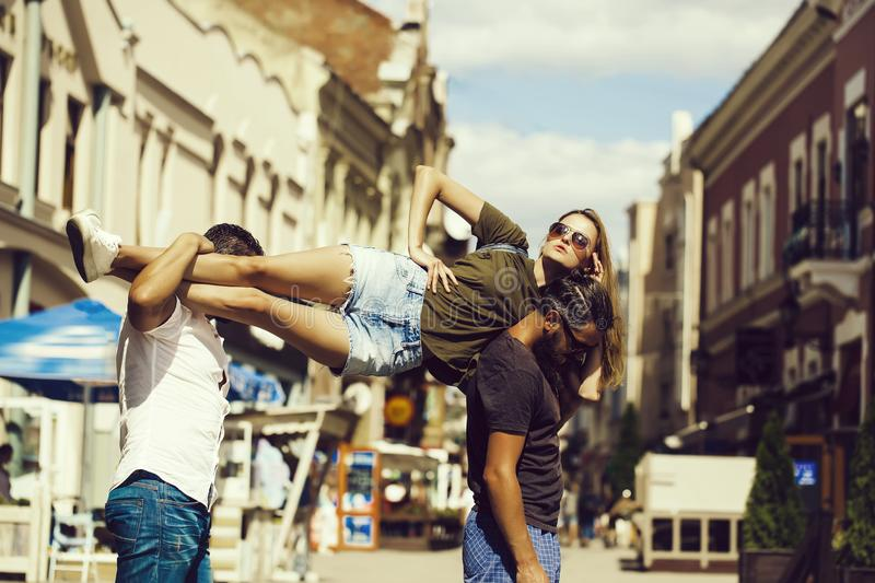 Two handsome men holding pretty girl on shoulders. Two handsome men holding pretty girl or beautiful women in sunglasses and jean shorts on shoulders on sunny royalty free stock photo