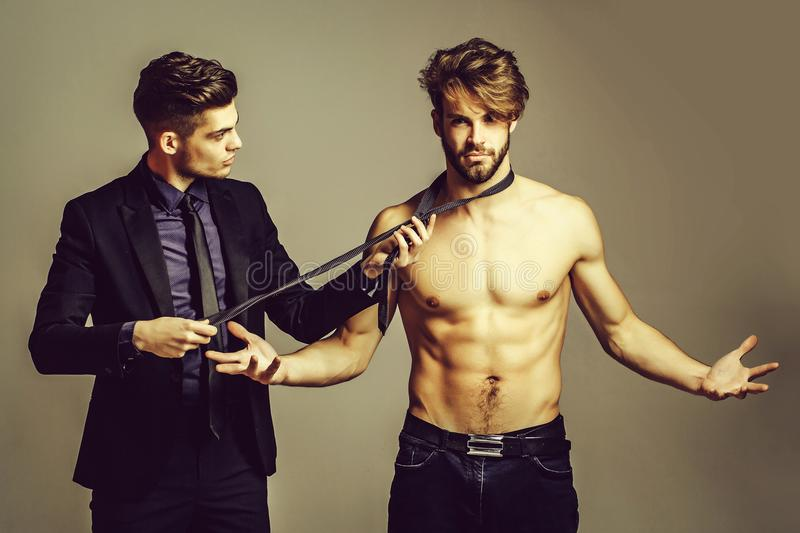 Two handsome men. Pose on grey background. Male model in businessman suit with tie. Muscular macho shows muscle torso with six packs and abs stock photo