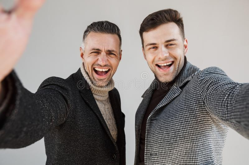 Two handsome men wearing coats over gray background royalty free stock photo