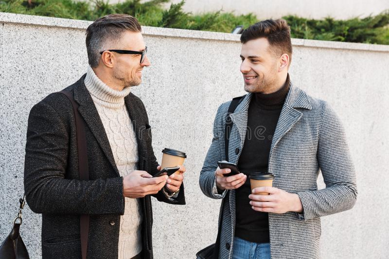 Two handsome men wearing coats spending time royalty free stock images