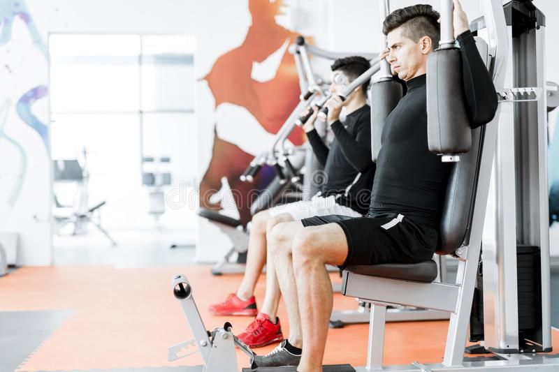 Young handsome men working out in a gym. Two handsome men working out in a beautiful fitness center stock photography