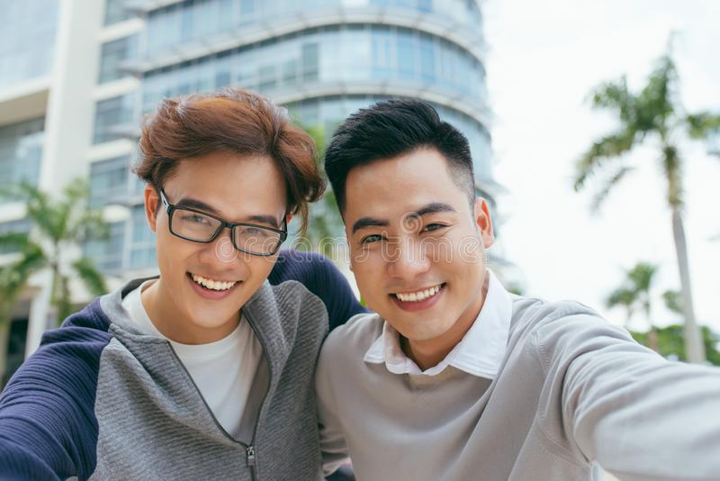 Two handsome and young asian men making selfie portrait on smartphone in the airport - Image stock photography