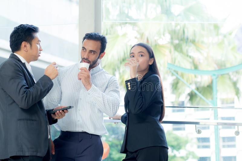 Two handsome young businessmen and lady in classic suits are holding cups of coffee. stock photos