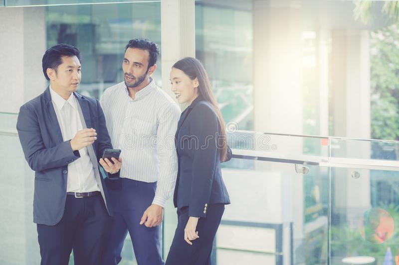 Two handsome young businessmen and lady in classic suits are holding cups of coffee, talking and smiling stock photo