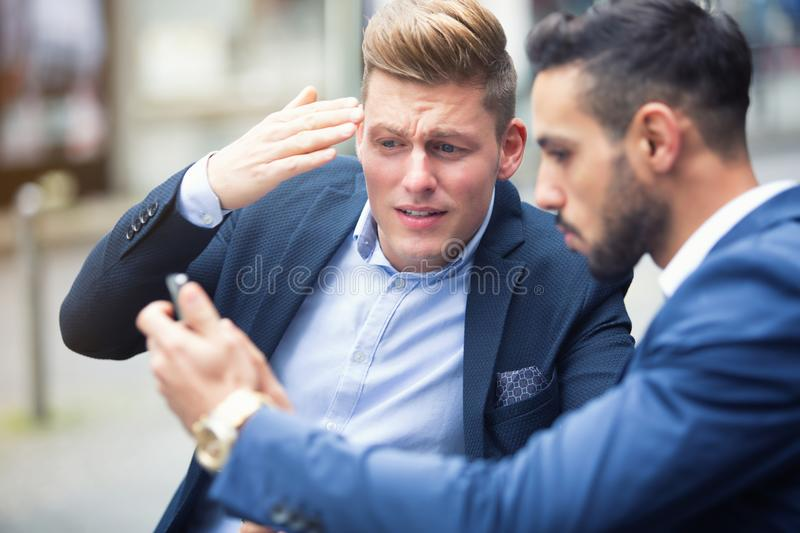 Two businessmen standing outside and looking at phone royalty free stock photography