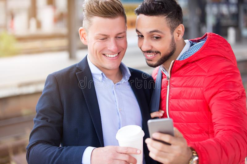Two businessmen standing outside and looking at phone royalty free stock photo