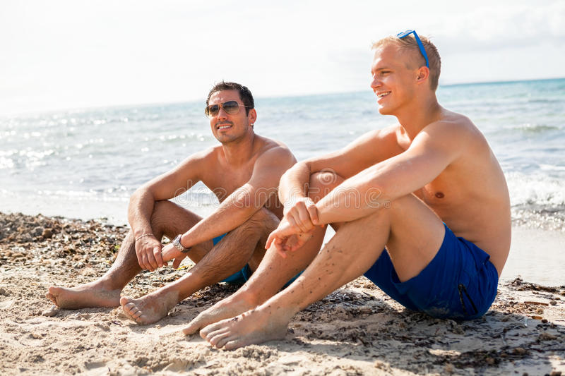 Two handsome young men chatting on a beach. In their swimsuits sitting side by side on the sand with their backs to the ocean enjoying a relaxing summer day at royalty free stock image