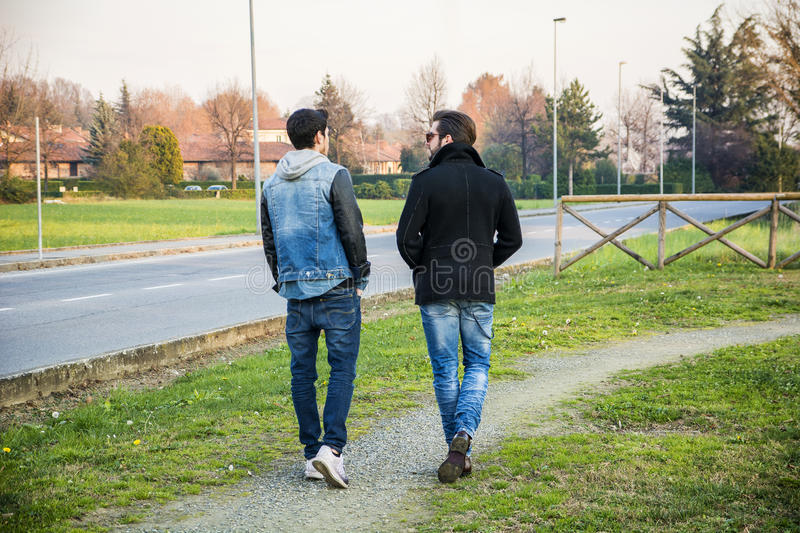 Two handsome young men, friends, in a park. Two handsome casual trendy young men, 2 friends, in an urban park walking and chatting together stock photos