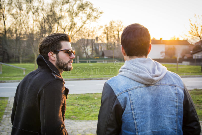Two handsome young men, friends, in a park. Two handsome casual trendy young men, 2 friends, in an urban park walking and chatting together stock image
