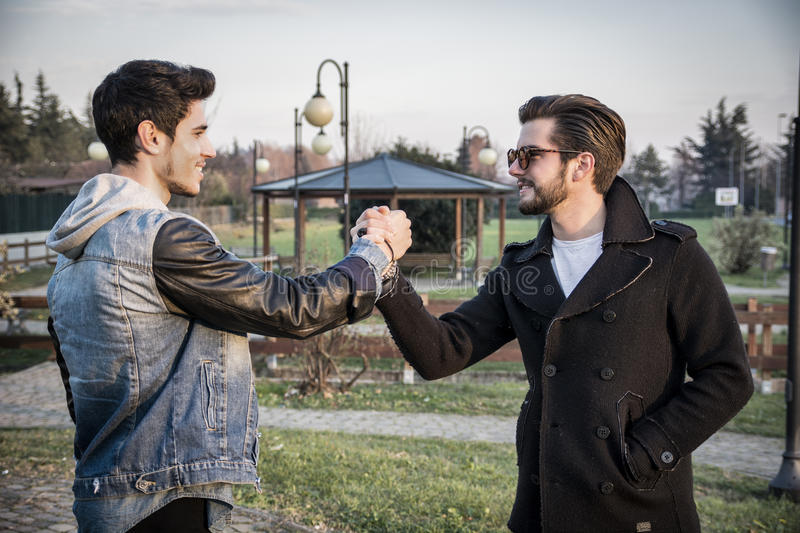 Two handsome young men greeting in a park. Two handsome casual trendy young men greeting outdoors in an urban park gripping hands with happy welcoming smiles stock images