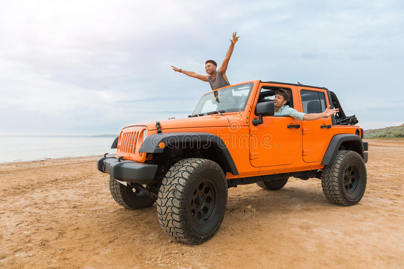 Two handsome young men having fun while driving. A car at the beach stock photo