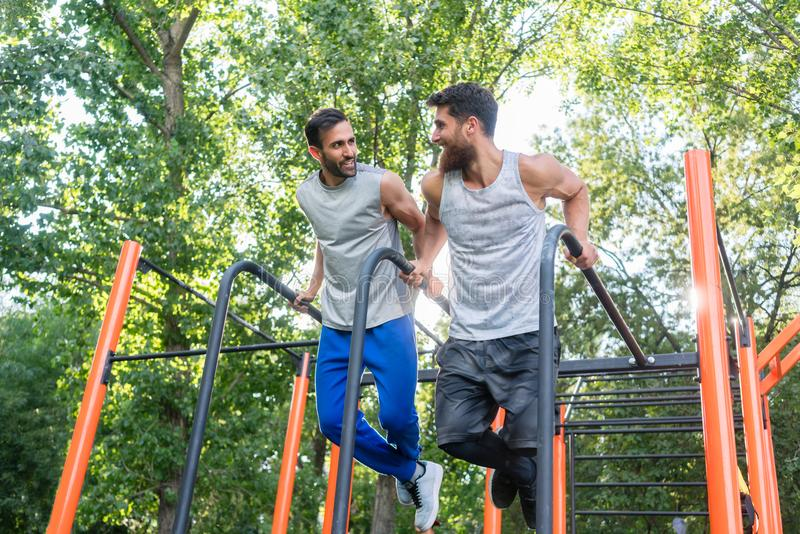 Two handsome young men passionate about fitness doing dips exerc. Low-angle view of two handsome young men passionate about fitness doing dips exercise for royalty free stock photo