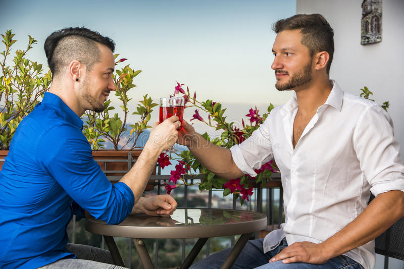 Two handsome young men sitting at the table with wine. SIde view of two stylish handsome men sitting at the table with glasses of wine while looking face to face royalty free stock photo