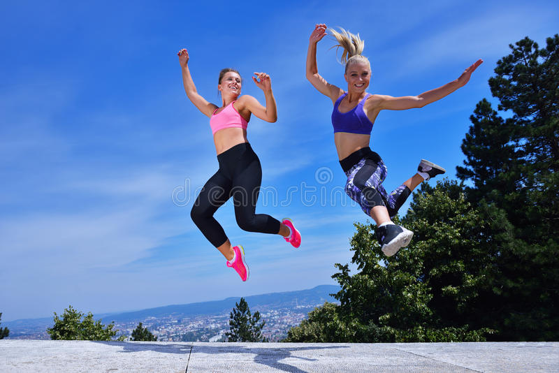 Two happiness young women jumping over blue sky.  royalty free stock image
