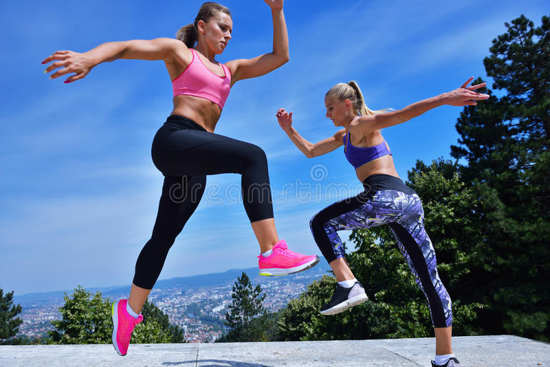 Two happiness young women jumping over blue sky.  stock image