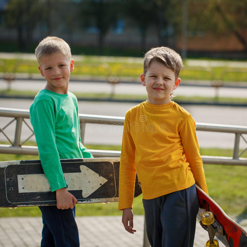 Two happy adorable boys, double portrait, boards hold in hand an royalty free stock photos