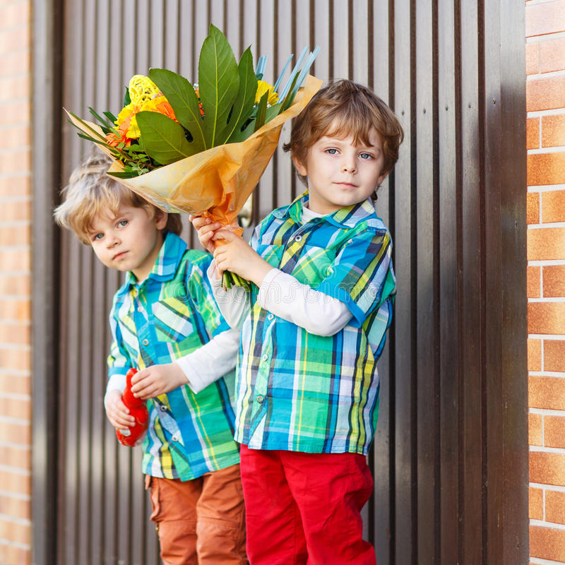 Two happy adorable little sibling boys with blooming flowers stock photo
