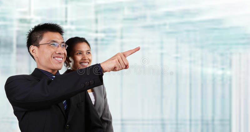 Two happy Asian business people. Two Asian business people pose together and the male pointing away his hand, with blur glass windows as background stock photos