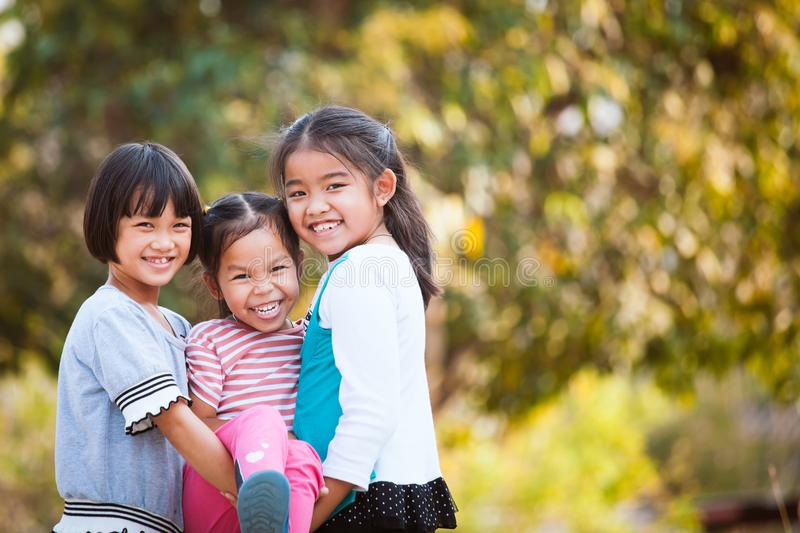 Two happy asian children carrying her sister stock photography