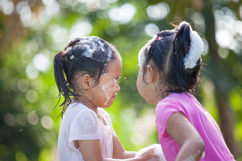 Two happy asian children girl having fun to bath. And play with foam together in outside stock photo
